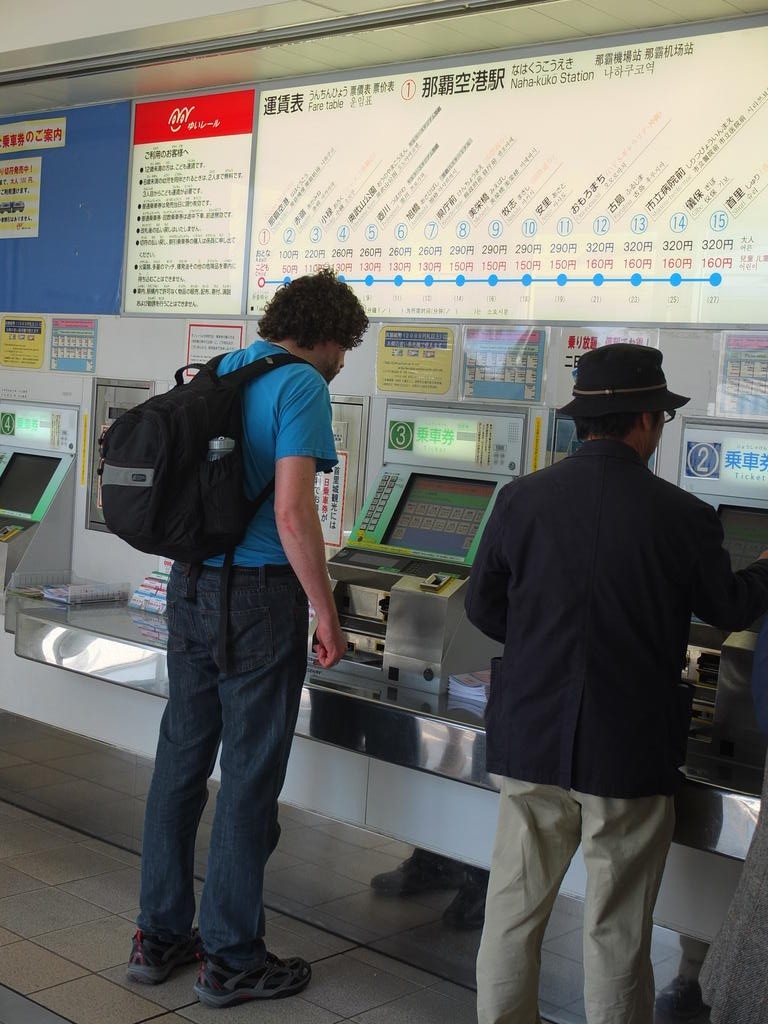 perplexe devant la machine à tickets